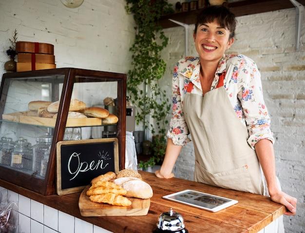 Mujer sonriente en el mostrador de la casa de madera hornear con tableta digital