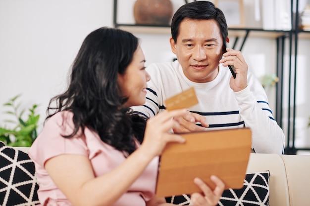 Mujer sonriente mostrando algo en la pantalla de la tableta cuando su marido llama al gerente de la tienda en línea