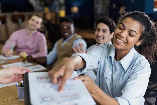 Mujer sonriente mostrando gráfico en la oficina con compañeros de trabajo