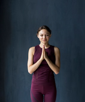 Mujer sonriente mostrando gratitud en una pose namaste