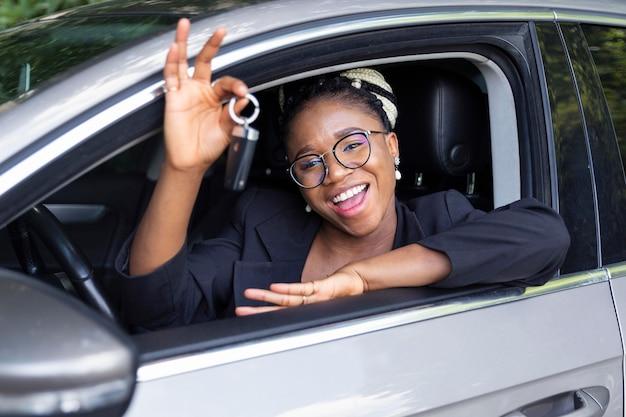Mujer sonriente mostrando las llaves de su coche mientras está sentado en él
