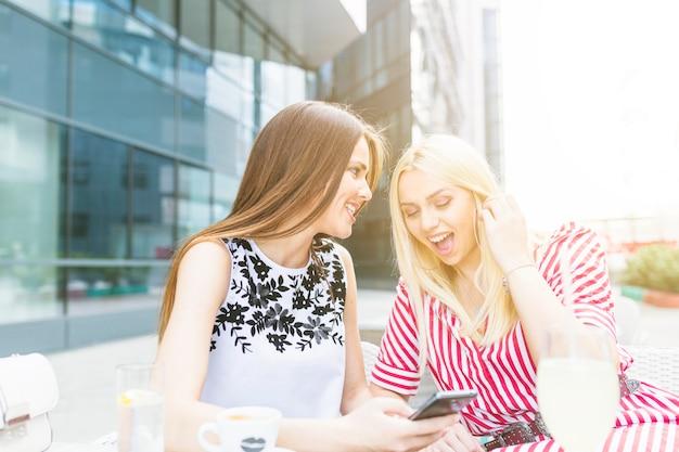 Mujer sonriente mostrando su móvil a su amiga sentada en el café al aire libre