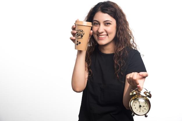 Mujer sonriente mostrando una taza de café con reloj sobre fondo blanco. foto de alta calidad
