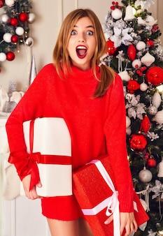 Mujer sonriente con muchas cajas de regalo posando cerca del árbol de navidad decorado