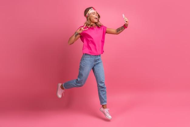 Mujer sonriente muy linda en accesorios de estilo hippie boho camisa rosa sonriendo diversión emocional posando en rosa
