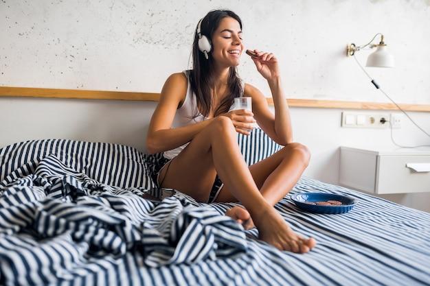 Mujer sonriente muy sexy sentada en la cama por la mañana, escuchando música en auriculares, desayunando, comiendo galletas y bebiendo leche, estilo de vida saludable
