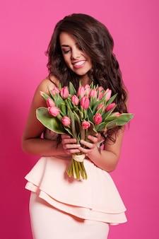 Mujer sonriente natural con ramo de tulipanes frescos