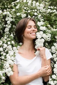 Mujer sonriente en la naturaleza que huele a flores