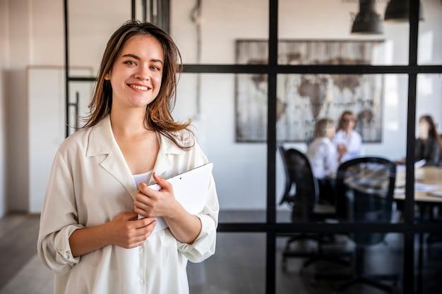 Mujer sonriente en la oficina trabajando en tableta