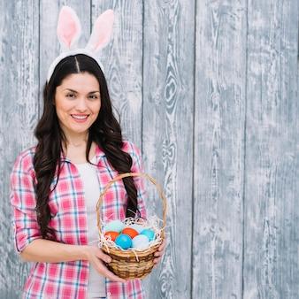 Mujer sonriente con los oídos del conejito en la cabeza que muestra la cesta de los huevos de pascua contra el contexto de madera