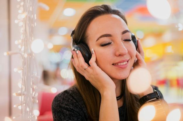 Mujer sonriente con los ojos cerrados con auriculares en la cabeza cerca de las luces de navidad