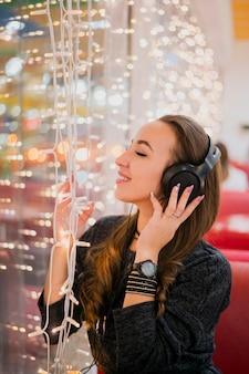 Mujer sonriente con los ojos cerrados con auriculares en la cabeza tocando las luces de navidad