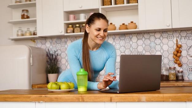 Mujer sonriente con ordenador en el interior de la cocina moderna. concepto de estilo de vida saludable y cocina. una mujer está buscando una receta o está transmitiendo en línea