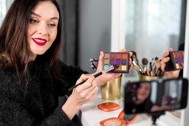 Mujer sonriente con paleta de maquillaje