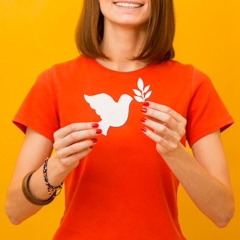 Mujer sonriente con paloma de papel