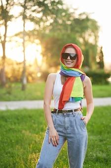 Mujer sonriente con pañuelo de arco iris en la cabeza.