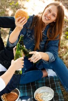 Mujer sonriente en el parque con hamburguesa y cerveza