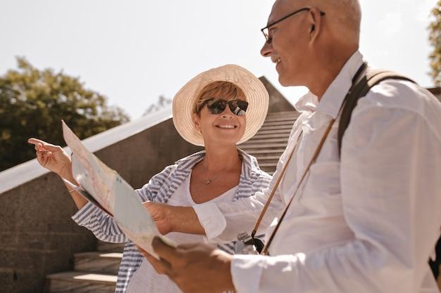 Mujer sonriente con pelo corto rubio con gafas de sol, sombrero y traje de rayas apunta a un lado y mira al hombre con mapa y cámara en camisa blanca al aire libre.