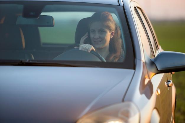 Mujer sonriente de pelo largo dentro de plata brillante coche conduciendo y hablando por teléfono móvil