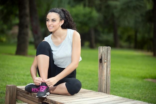 Mujer sonriente de pelo negro que ata los cordones de las zapatillas de deporte