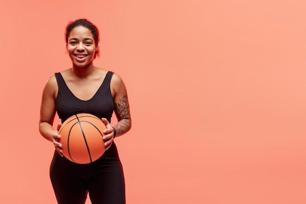 Mujer sonriente con pelota de baloncesto