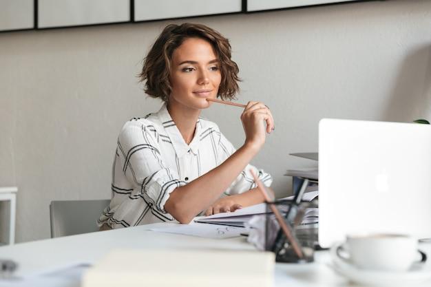 Mujer sonriente pensativa que trabaja junto a la mesa