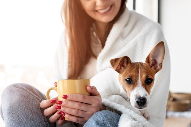 Mujer sonriente con perro en su regazo