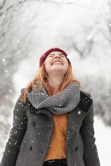 Mujer sonriente de pie en la nieve.