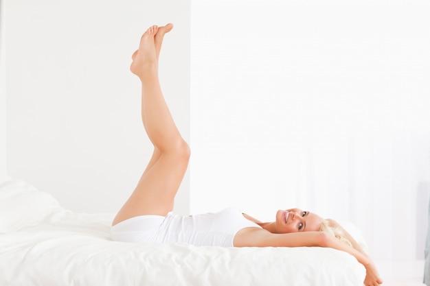 Mujer sonriente con las piernas para arriba