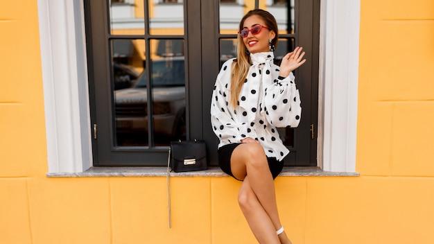 Mujer sonriente con las piernas en ropa elegante de primavera con bolso pequeño posando en la calle en amarillo.