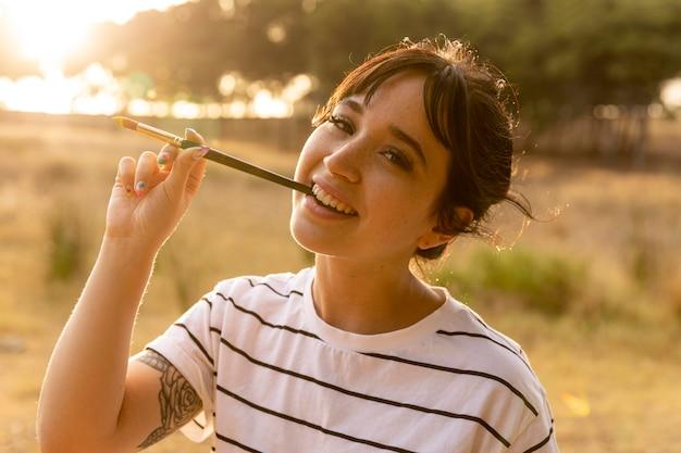 Mujer sonriente con pincel en la boca