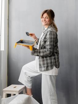 Mujer sonriente con pincel y pintura