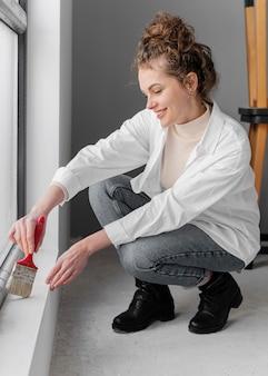Mujer sonriente pintando con pincel