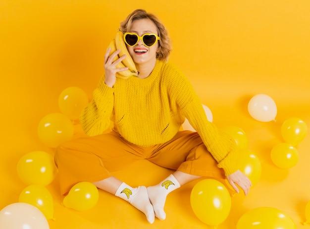 Mujer sonriente con plátanos como móvil
