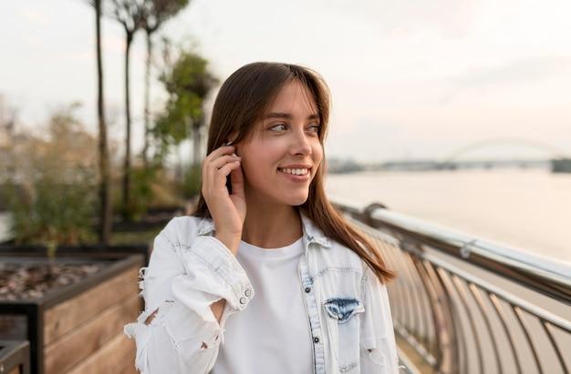 Mujer sonriente poniéndose auriculares mientras está al aire libre