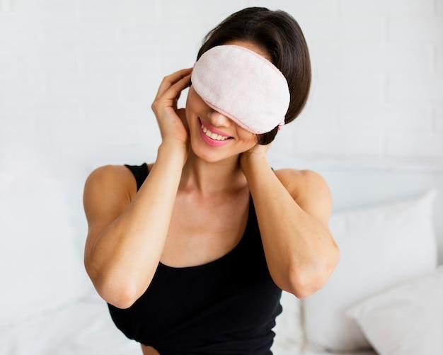 Mujer sonriente poniéndose máscara para dormir