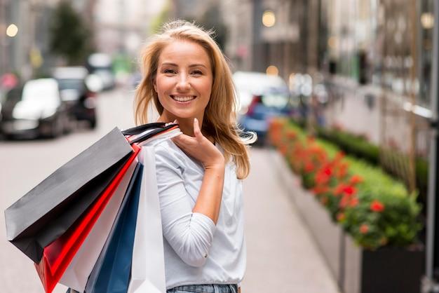 Mujer sonriente posando al aire libre con bolsas de la compra.
