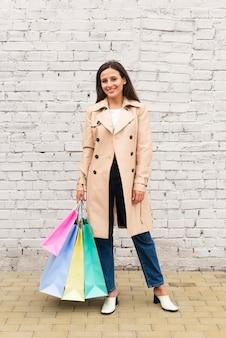 Mujer sonriente posando al aire libre mientras sostiene bolsas de la compra.