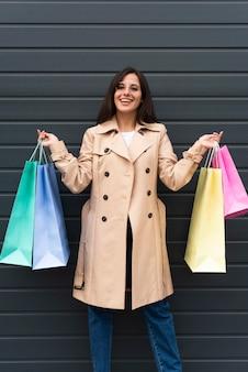 Mujer sonriente posando al aire libre y sosteniendo bolsas de la compra.
