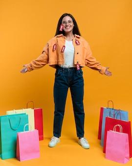 Mujer sonriente posando con bolsas de la compra y etiquetas de venta