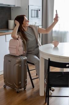 Mujer sonriente posando en la cocina tomando selfie con equipaje viaje de verano viajes vacaciones en la cocina