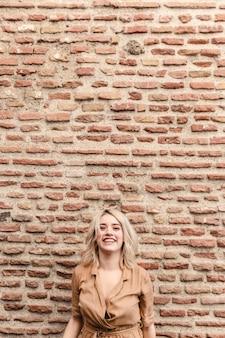 Mujer sonriente posando contra la pared de ladrillo con espacio de copia