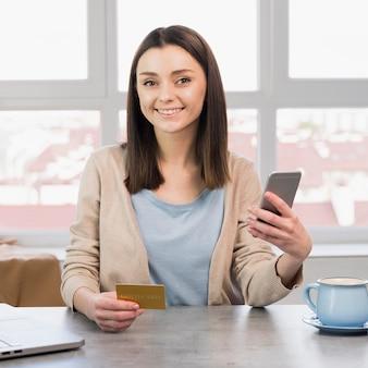 Mujer sonriente posando en el escritorio con teléfono inteligente