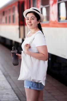 Mujer sonriente posando en la estación de tren