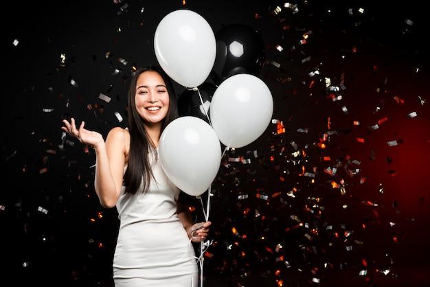 Mujer sonriente posando con globos en fiesta de año nuevo
