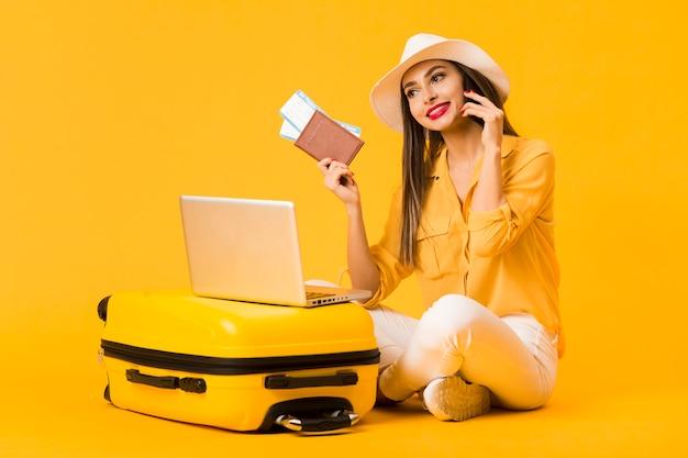 Mujer sonriente posando junto al equipaje mientras sostiene boletos de avión y pasaporte