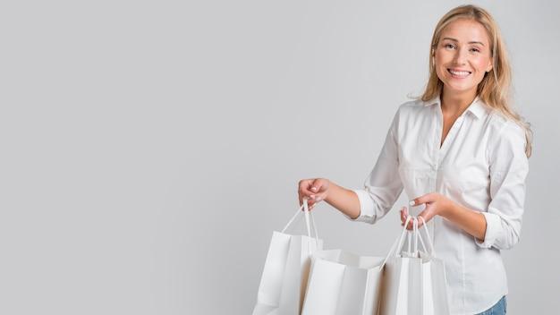 Mujer sonriente posando mientras sostiene bolsas de compras con espacio de copia