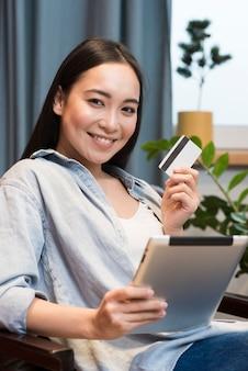 Mujer sonriente posando mientras sostiene la tableta y tarjeta de crédito