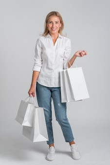 Mujer sonriente posando con un montón de bolsas de la compra.