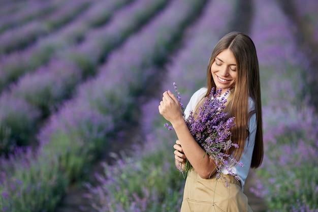 Mujer sonriente posando con ramo de flores en campo lavanda
